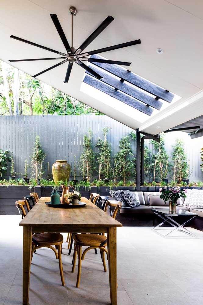 Espaço gourmet coberto com jardim no canteiro verde