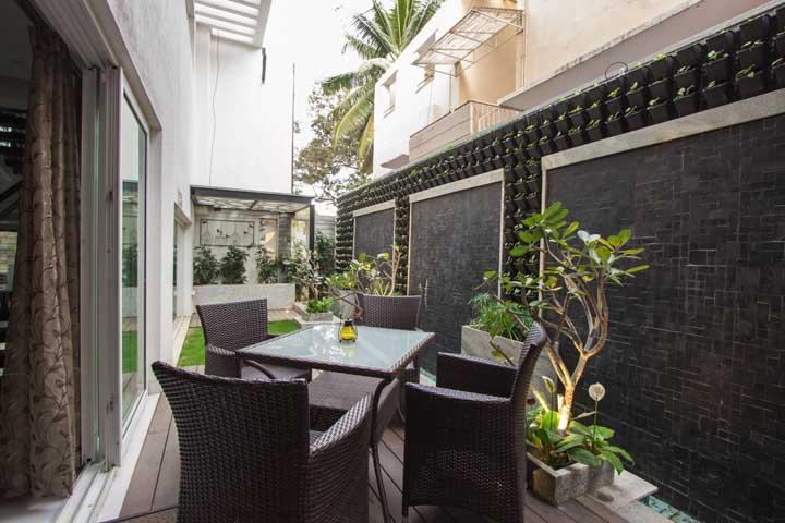 A varanda ganhou a companhia de um pequeno jardim de vasos no chão e um jardim vertical em formação na parede