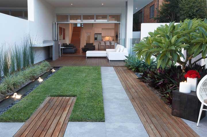 Deck de madeira, mini lago, iluminação direcionada e gramado: fórmula para um jardim residencial incrível
