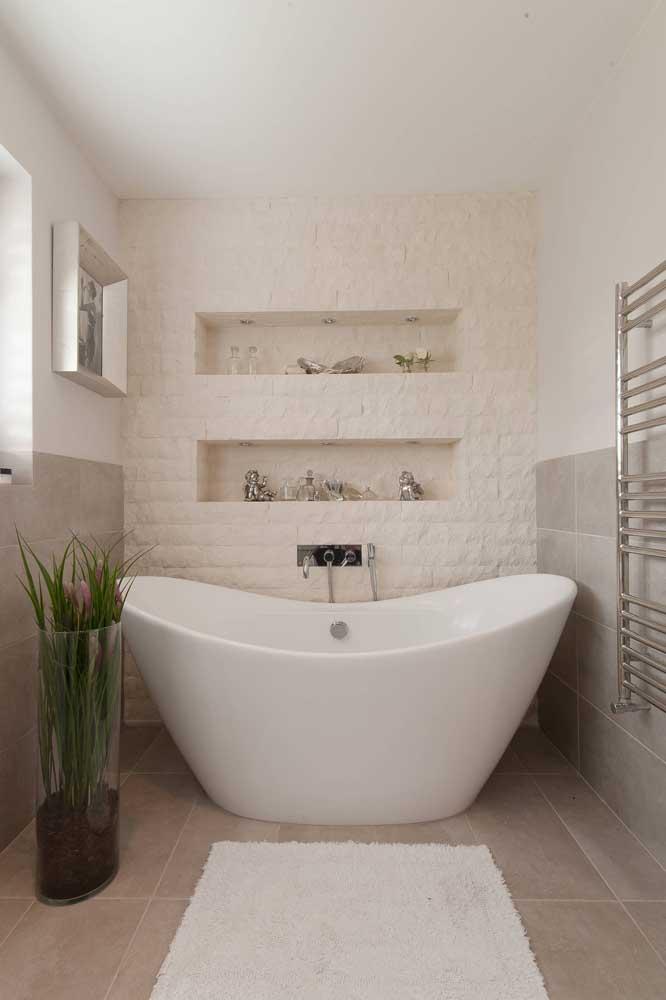 A parede desse banheiro com revestimento 3D contou com a funcionalidade dos dois nichos embutidos e iluminados com spots