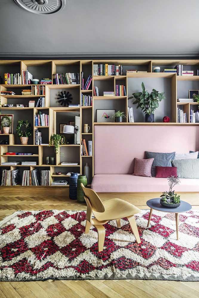Nessa sala de estar, os nichos revestem toda a parede e servem para acomodar livros, discos e plantas