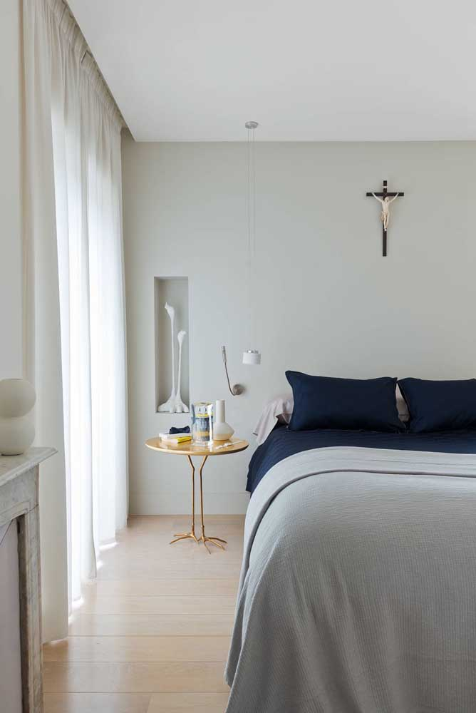 Esse quarto de decoração neutra conta com um nicho de parede retangular para acomodar o vaso decorativo