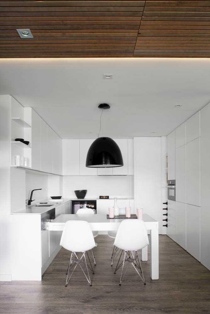 Nessa cozinha, a mesa de parede forma um L e ajuda a demarcar o espaço
