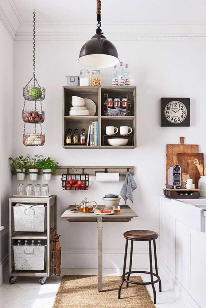 Tudo muito pequeno, mas bem organizado nessa cozinha com mesa de parede