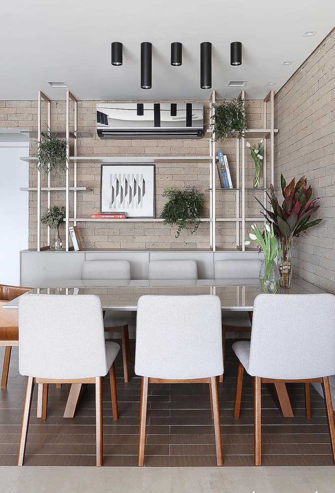 As cadeiras estofadas dão o toque de glamour a essa sala de jantar com mesa de parede