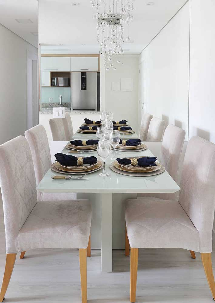 Não se deixe levar pelas aparências: a mesa alongada que você vê na imagem, nada mais é do que a mesa real sendo refletida na parede espelhada, um belo truque, não?