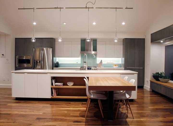 Mesmo ampla, essa cozinha integrada a sala de jantar apostou na modernidade da mesa de parede, que, nesse caso, vem apoiada no balcão