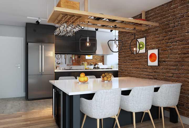 Esse ambiente integrado de estilo industrial apostou em uma mesa de parede preta com espaço para frigobar na parte lateral