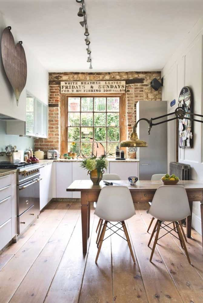 Mesa rústica de madeira encostada na parede; as cadeiras estilo Eames completam a decor