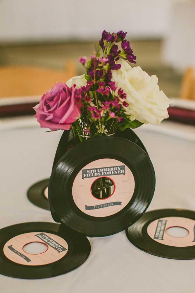 Que tal um arranjo de flores para o centro da mesa feito com discos de vinil?