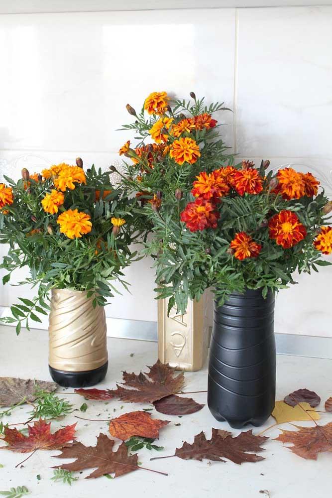 A inspiração aqui é muito simples: pegue garrafas de plástico de formatos variados e corte na altura que desejar, depois pinte-as com tinta spray e coloque suas flores favoritas dentro