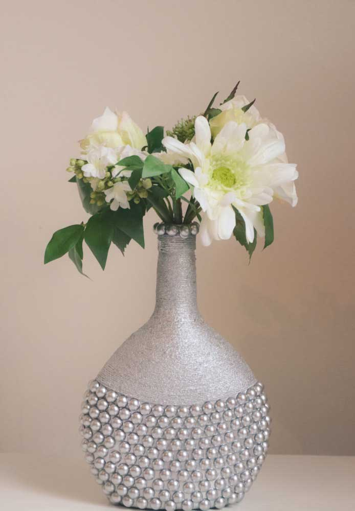 O vaso decorativo dessa casa foi feito com garrafa de vidro decorada com barbante e pérolas que depois recebeu acabamento em tinta prata