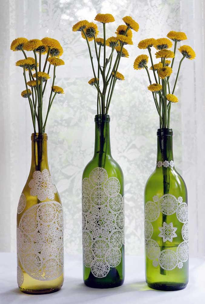 Garrafas de vidro decoradas com renda funcionando aqui como vaso para as flores de corte
