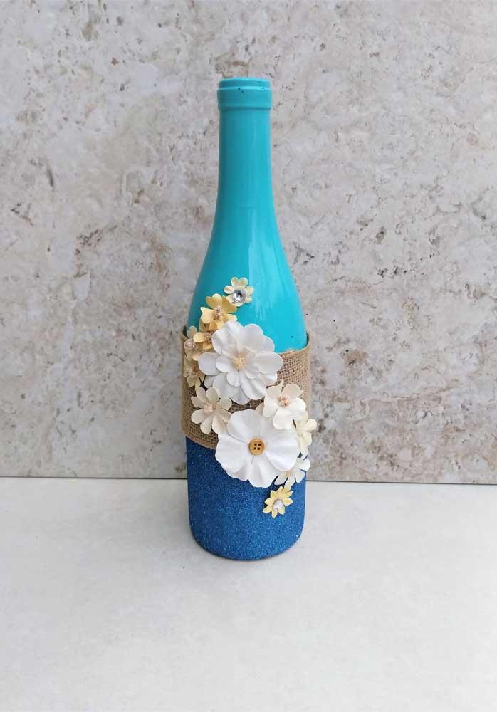 Linda sugestão de garrafa decorada na cor azul com detalhe em juta e flores de tecido; ideal para casamentos