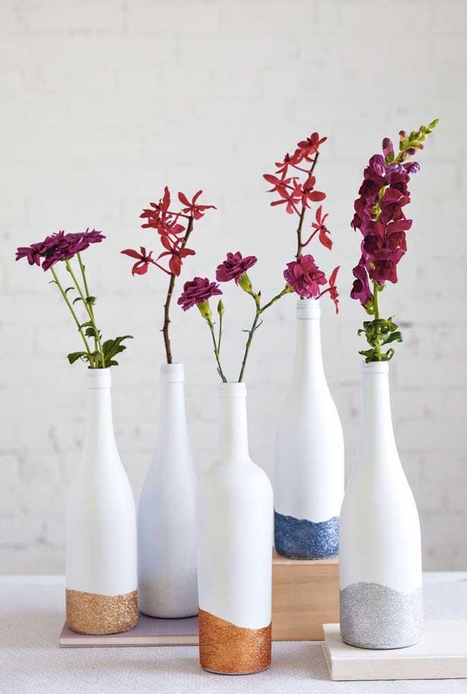 Garrafas de vidro pintadas de branco e decoradas com gliter na base; repare que o mix de formatos garantiu um visual descontraído ao conjunto