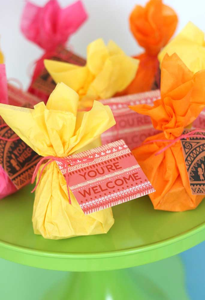 Em uma lembrancinha mais simples, coloque algumas guloseimas em um saquinho de papel, amarre com fita e coloque um cartão para identificar
