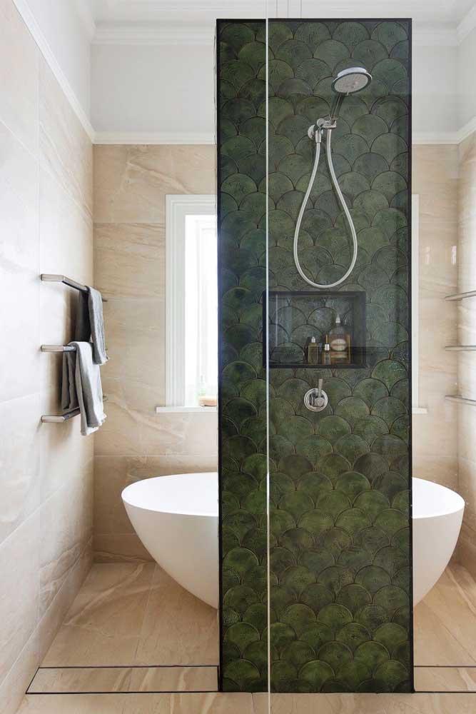 O revestimento em diferentes tons de verde musgo marca a área do banho