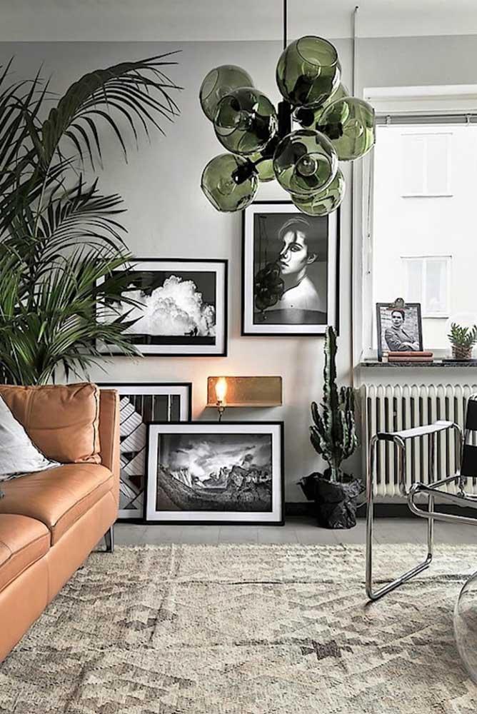 Que tal uma luminária de vidro em verde musgo para sala de estar? O tom de verde segue na decoração com a presença do vaso de palmeira areca
