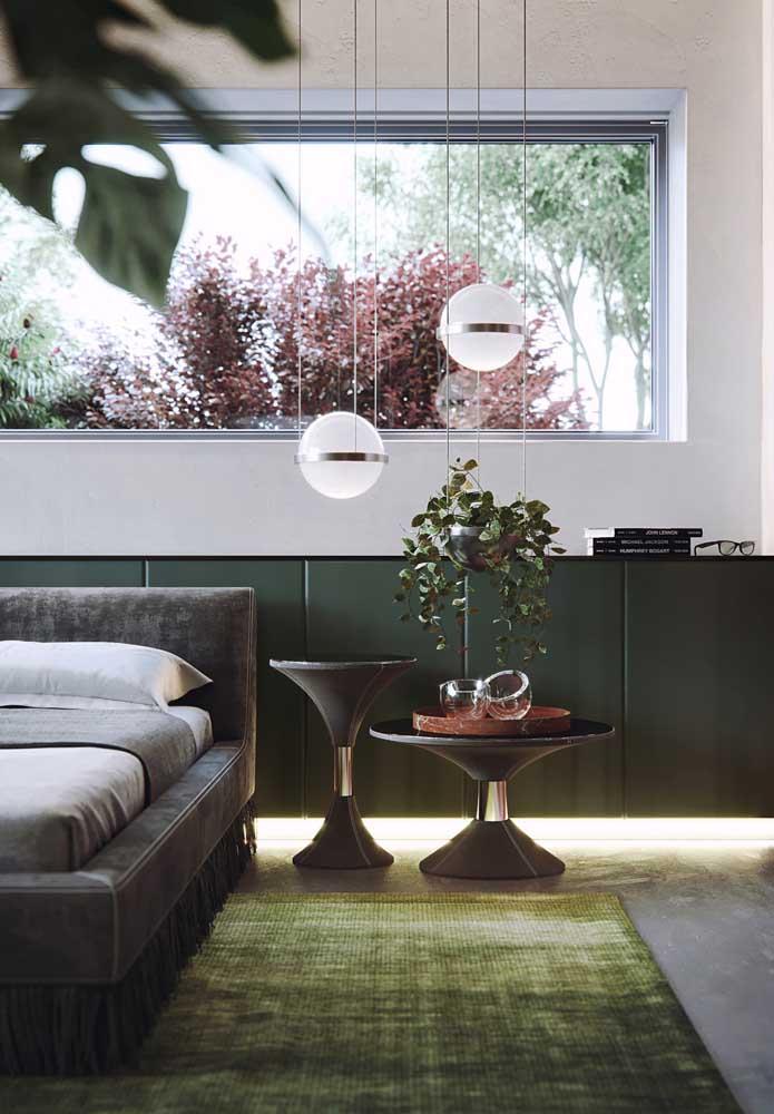 Sala de estar decorada com dois tons de verde musgo: o mais escuro no armário lateral e um mais vibrante e quente no tapete