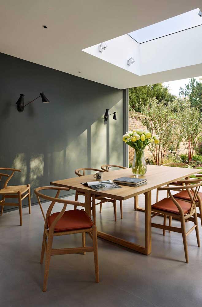 A iluminação natural traz ainda mais frescor para a sala de jantar em tons de verde musgo e madeira
