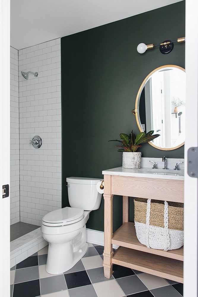 Perfeita a pintura dessa parede verde musgo; a combinação com o branco e os elementos de fibra naturais deixaram o pequeno banheiro ainda mais incrível