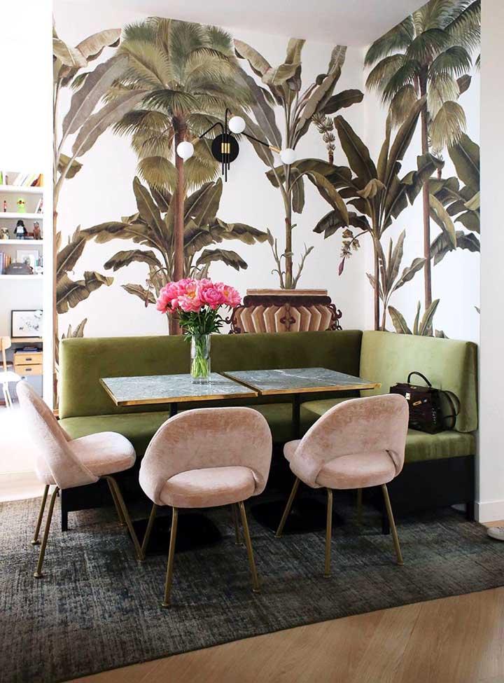 Canto alemão com sofá de veludo verde musgo e cadeiras cor de rosa; o papel de parede com plantas tropicais finaliza a proposta