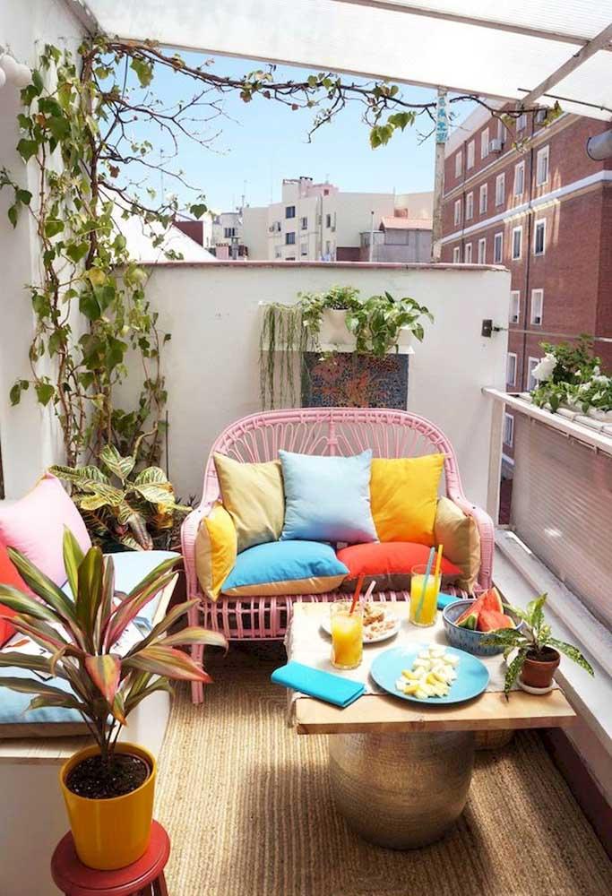 Para essa varanda simples de apartamento, a solução foi apostar em uma namoradeira de fibra colorida e cheia de almofadas