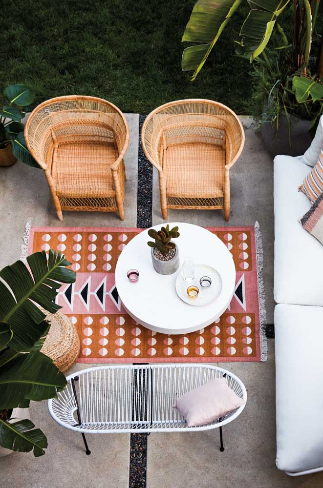 Namoradeira para área externa inspirada no estilo das cadeiras Acapulco; para completar o cenário, poltronas de fibra natural