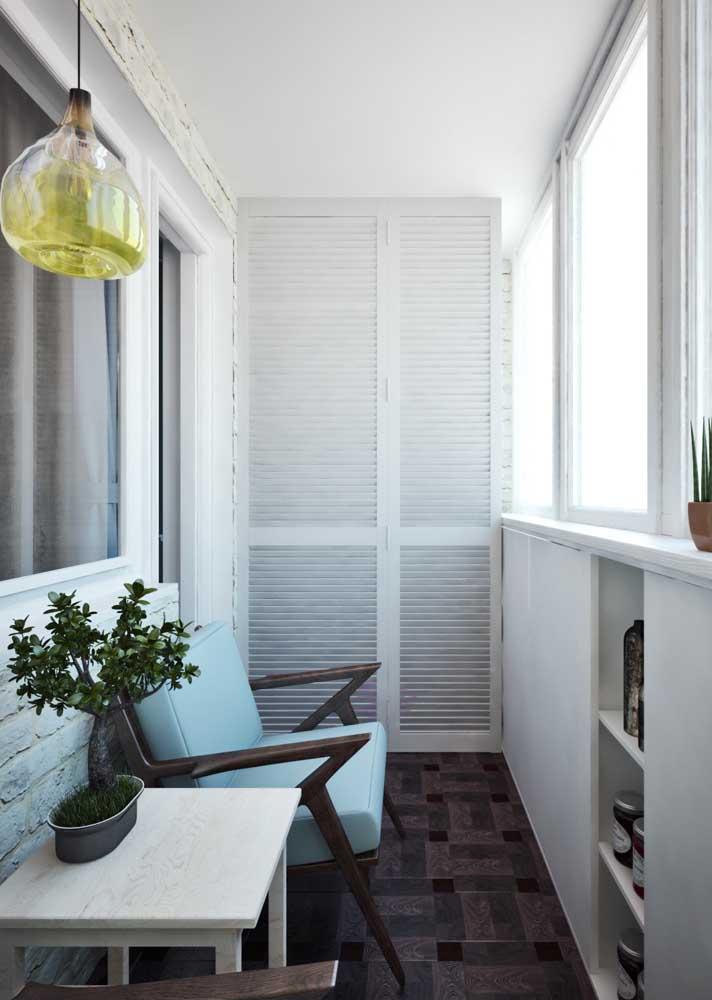 A pequena varanda desse apartamento conta com o charme e a elegância da namoradeira em estilo moderno