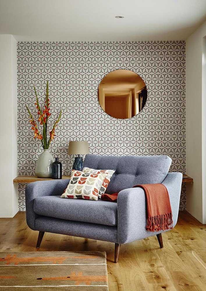 Namoradeira confortável e aconchegante de linho azul em contraste com a parede geométrica aos fundos