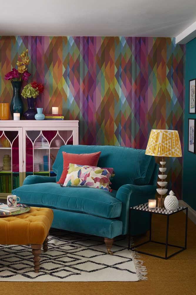 A sala de estar vibrante e colorida acertou em cheio na escolha da namoradeira azul em veludo