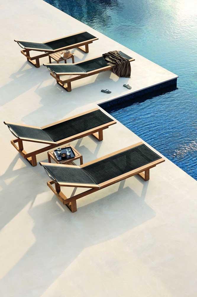Conjunto de espreguiçadeiras de fibra sintética na cor preta com bordas em madeira; conforto e beleza na beira da piscina