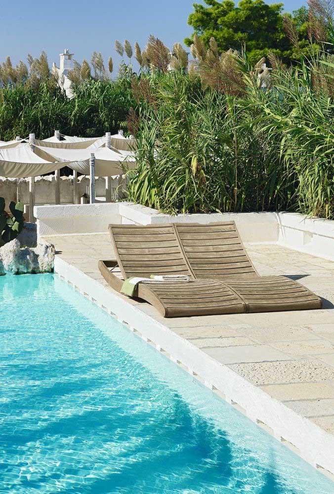 Par de espreguiçadeiras de madeira simples para relaxar à beira da piscina