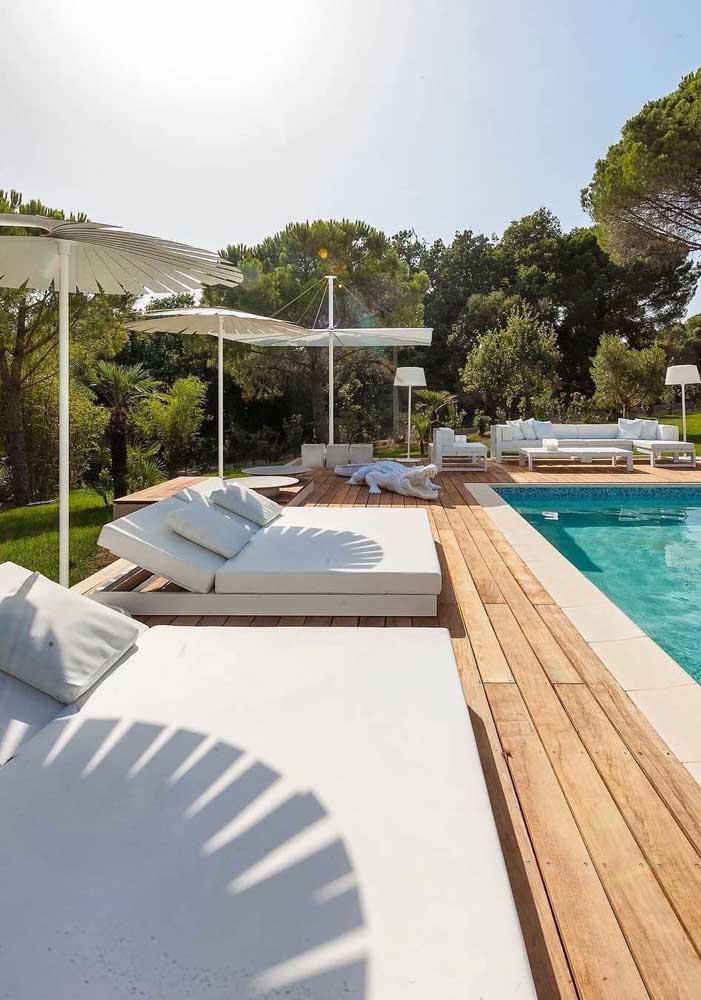 O entorno de toda a piscina é feito por espreguiçadeiras com ombrelones