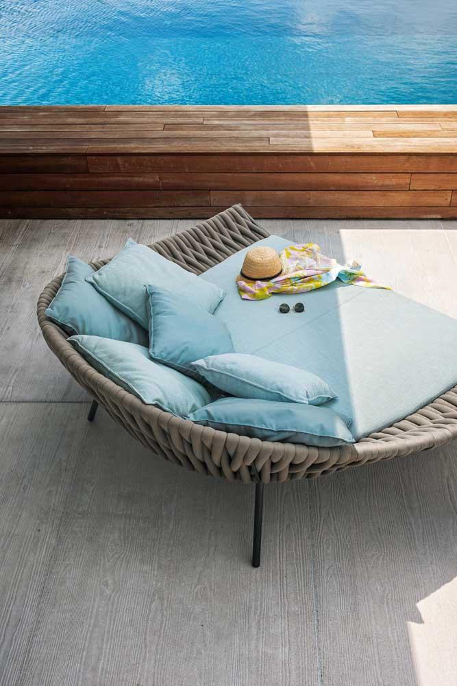 Espreguiçadeira redonda com muitas almofadas para garantir momentos super relaxantes; o tom azul suave do móvel é um destaque a parte