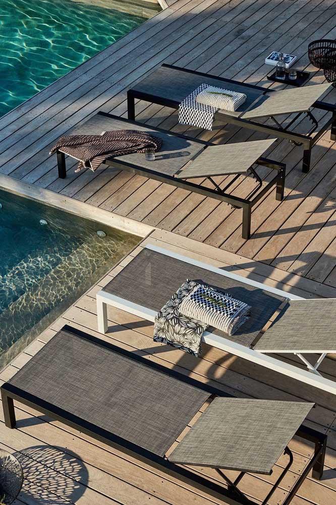 O deck de madeira na beira da piscina recebeu muito bem as espreguiçadeiras de lona com regulagem de altura