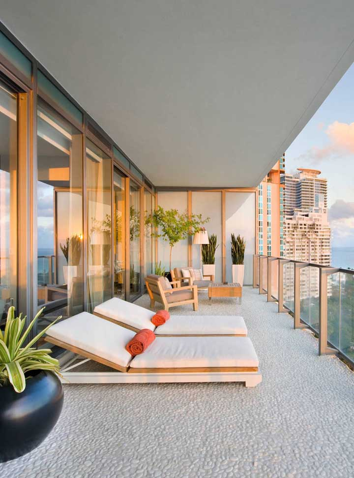 Para essa varanda ampla e arejada, uma dupla de espreguiçadeiras estofadas muito confortáveis