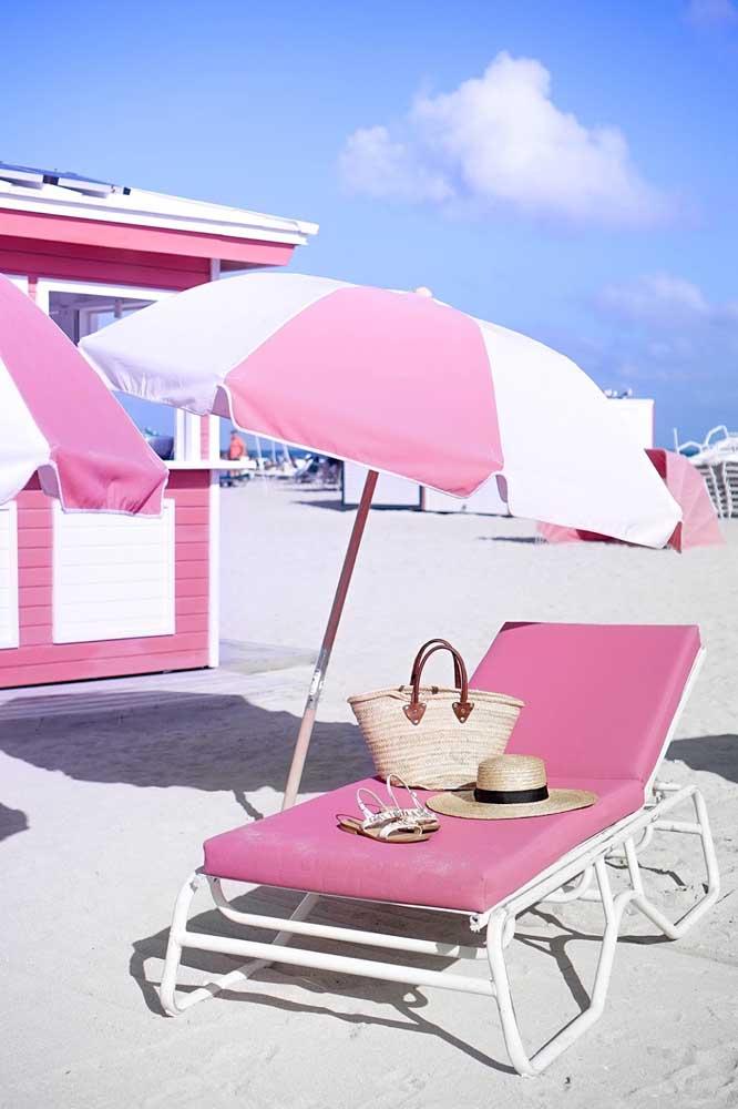 Espreguiçadeira rosa para praia; para combinar, um guarda sol na mesma cor