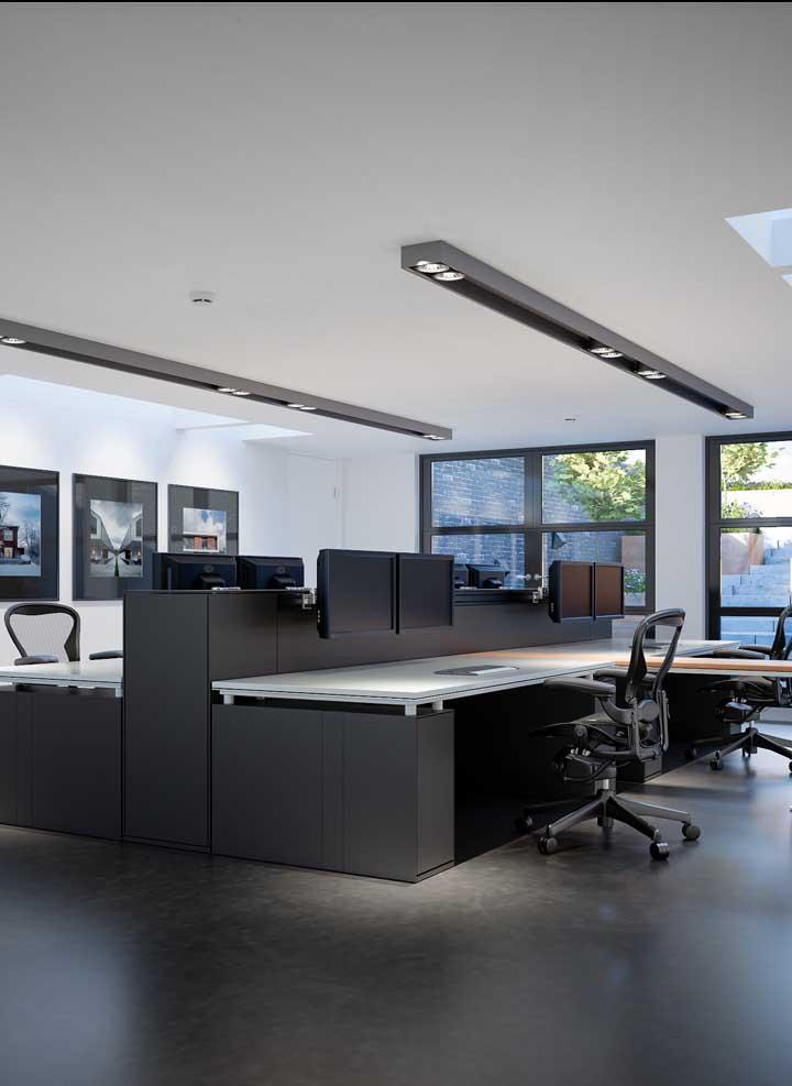 Escritório grande com mesas largas, planejadas para quem precisa de muito espaço para trabalhar