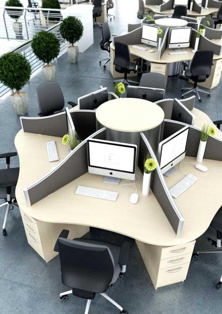 Aqui, mesas redondas grandes foram divididas em baías para atender a demanda de funcionários do escritório grande e moderno
