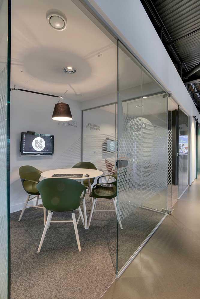 Sala de reunião em vidro com mesa e cadeiras modernas; modelo ideal para agências de publicidade e comunicação