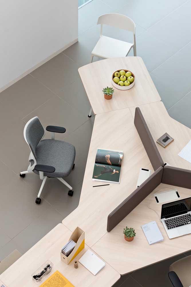 Mesa em madeira, com formato diferenciado, caracteriza esse escritório inovador