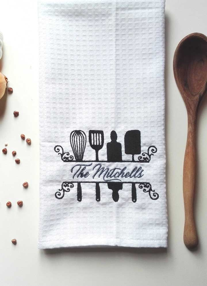 Aqui, o pano de prato traz o nome da família bordada entre os utensílios da cozinha