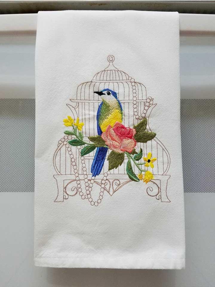 O passarinho azul é o destaque desse pano de prato ricamente bordado