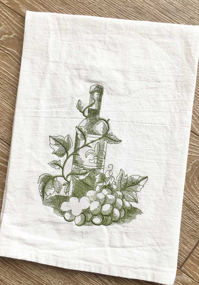 Uma única cor dá conta desse bordado que estampa uma garrafa de vinhos e uvas no pano de prato