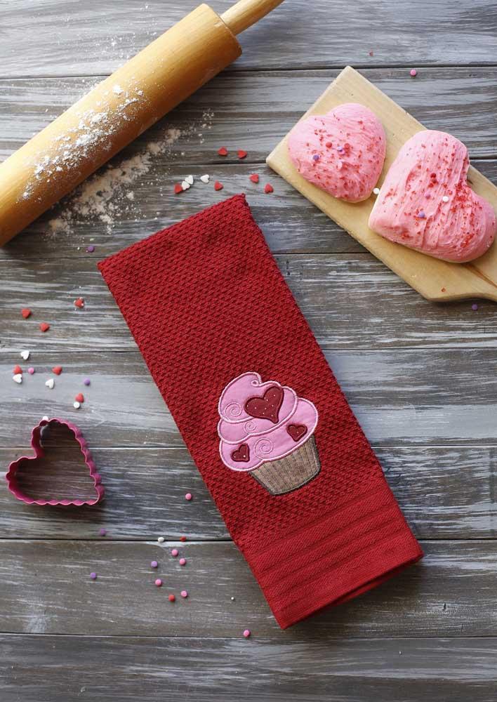 O pano de prato vermelho recebeu o gracioso bordado de cupcake
