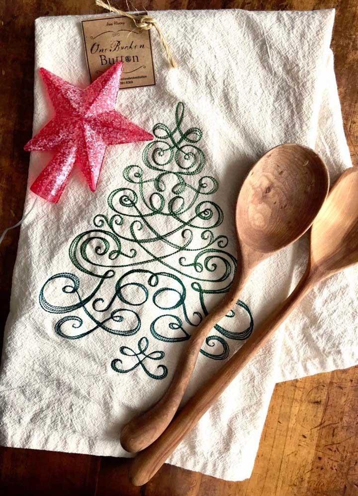Uma árvore de natal toda estilizada é o tema desse pano de prato bordado para o natal