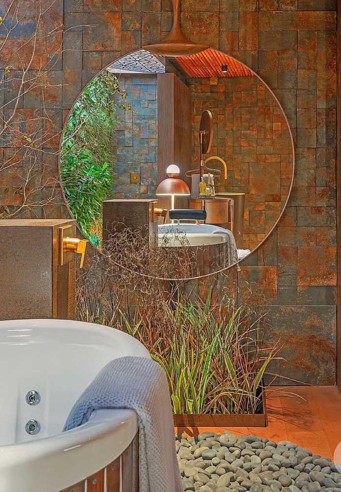 O banheiro em tons terrosos ficou incrível com a parede de Pedra ferro junto ao espelho redondo com borda infinita