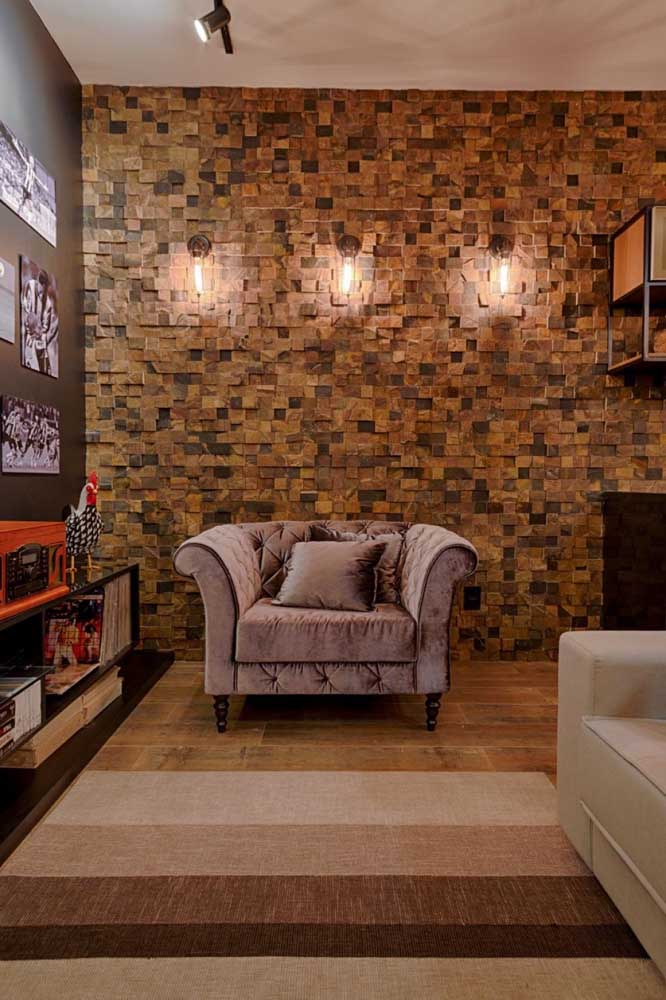 O ar intimista da sala de estar foi potencializado pela aplicação da Pedra ferro, além das arandelas que deixaram o espaço mais aconchegante