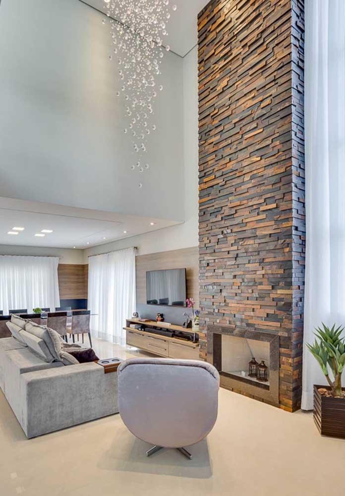 Nessa sala de estar, a Pedra ferro destaca tanto a lareira, quanto o pé direito alto da casa